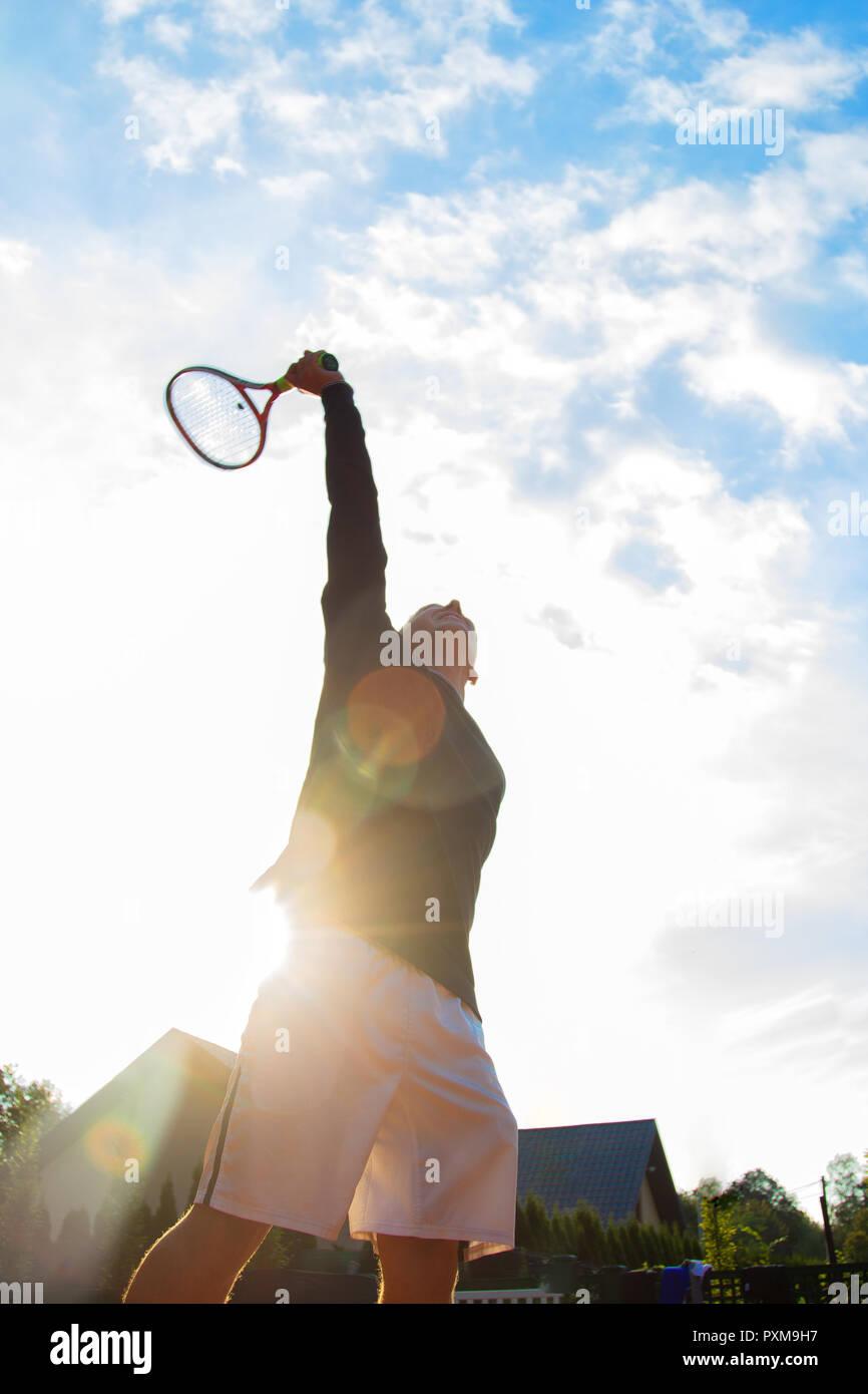Tenista profesional jugando un partido de tenis en una cancha. Él está a punto de golpear la bola con la raqueta. Foto de stock