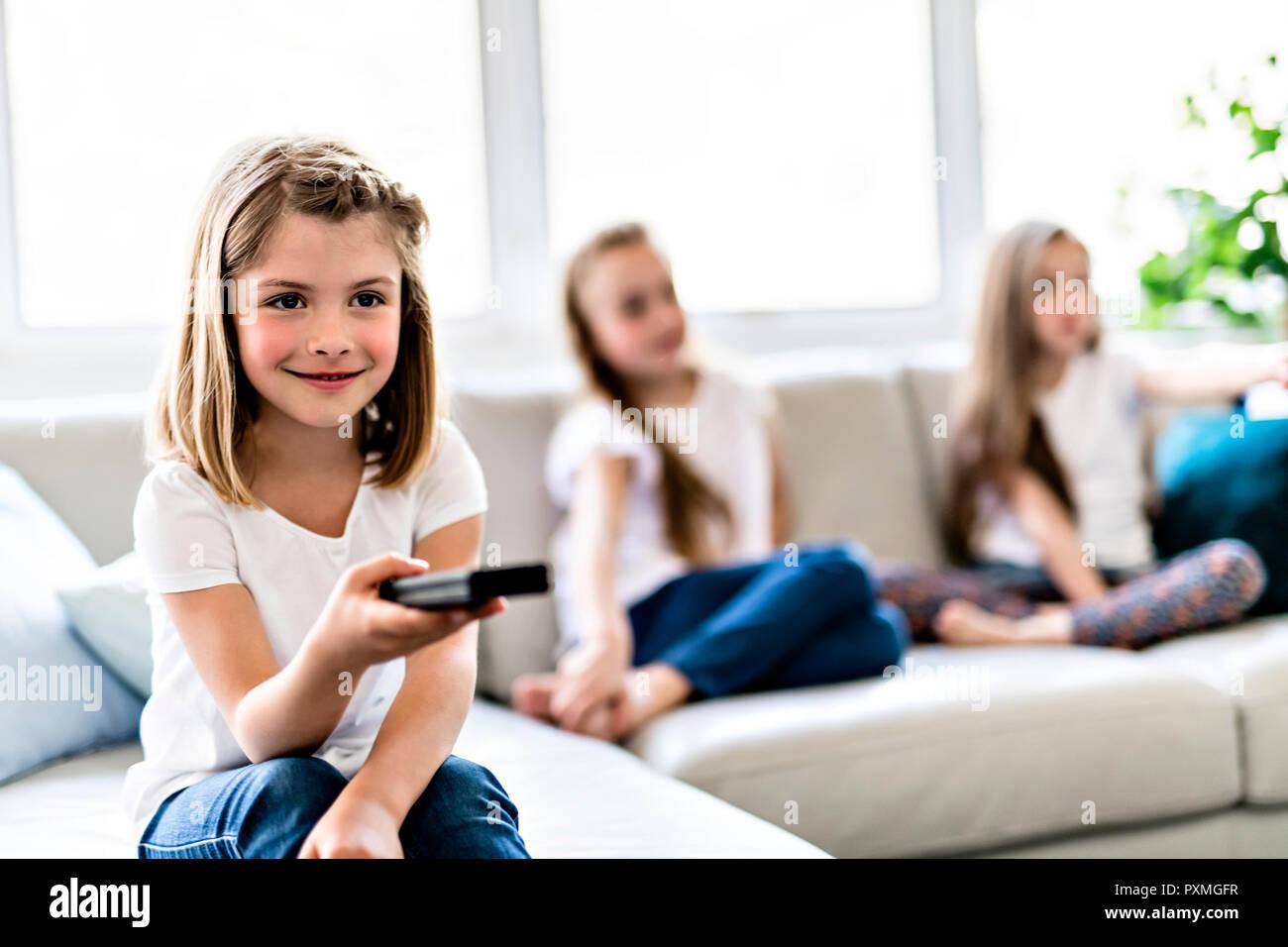 f3cfbd695 Tres atractivas childs las niñas en ropa casual viendo la televisión en casa  bonita Imagen De