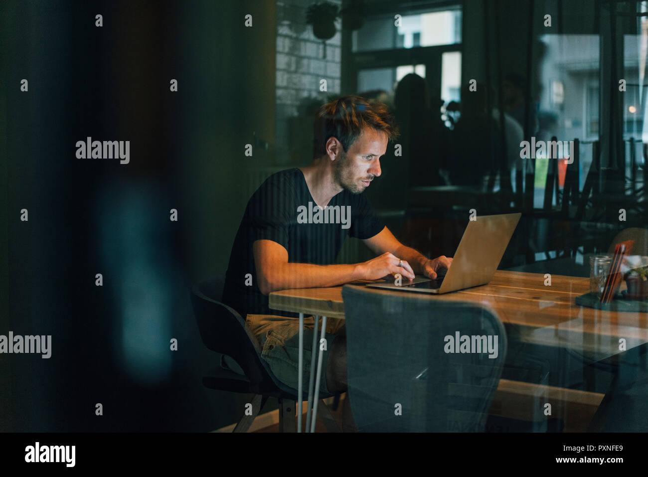 Hombre sentado en la oficina, trabajando tarde en su puesta en marcha de la empresa Foto de stock