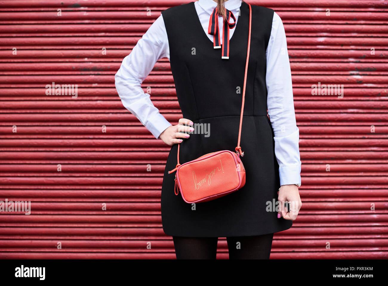 Moda Mujer con bolso rojo vestidos de traje negro de pie en