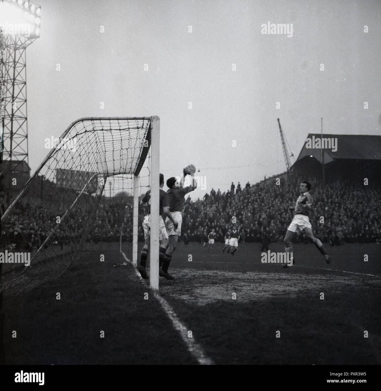 """1950, histórica, tarde y goalmouth acción en un partido de fútbol en la Antigua guarida, New Cross, Londres SE14, la casa de Millwall FC, establecido en 1885. La gran extensión de terreno que se abrió en 1910 y mientras esté en uso era conocido como el """"Den"""", podría tener más de 47.000 espectadores, con más de 43.000 de estos parados. Foto de stock"""