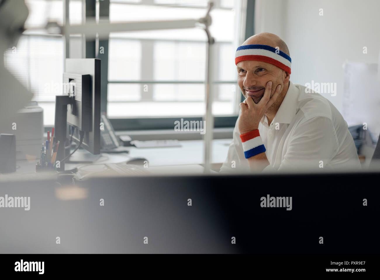 Hombre de negocios sentado en la oficina, usando bandas de sudor Imagen De Stock