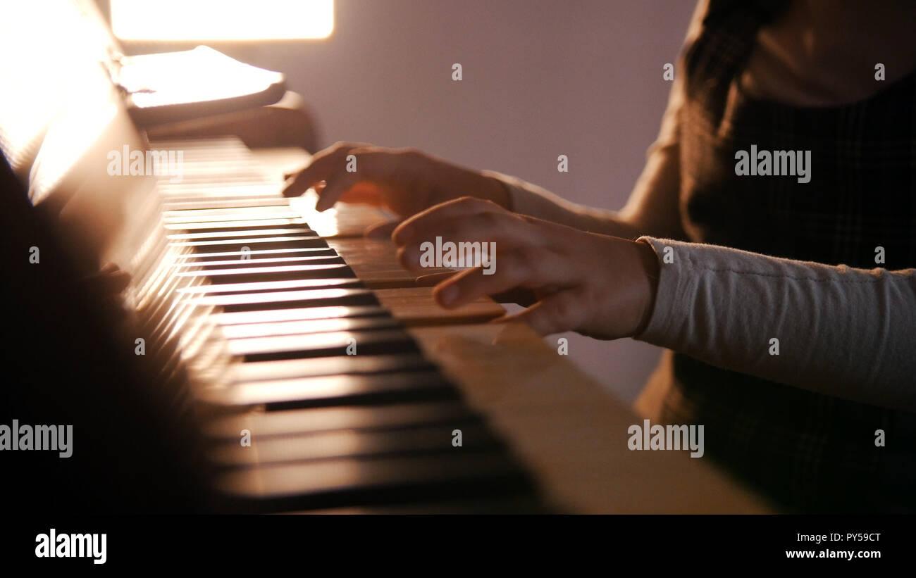 Un bebé tocando el piano en la lección de música. Hermoso sol Foto de stock