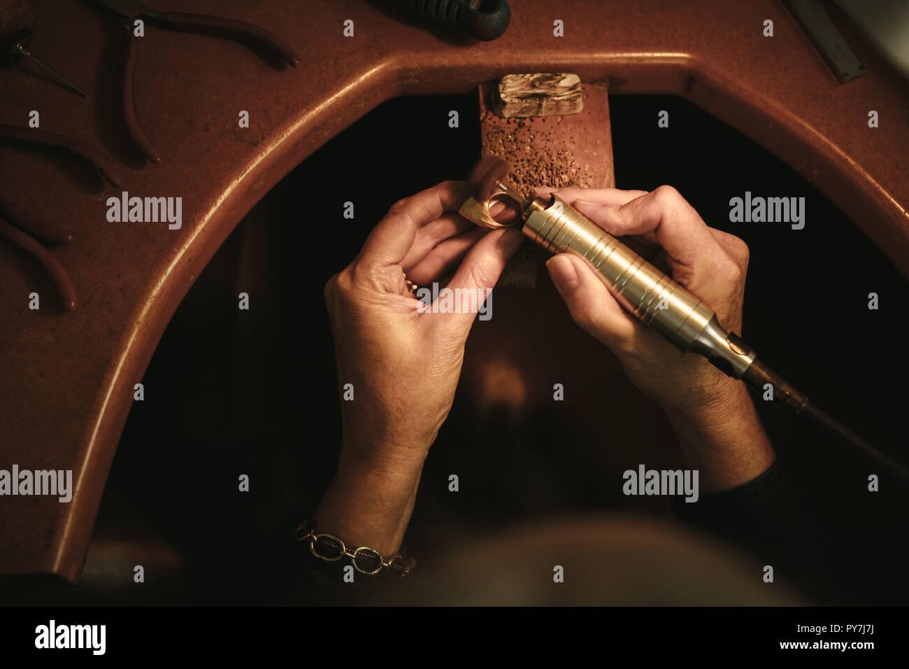 7d4b59f80cdf Cerca de joyero femenino manos pulir un anillo en su banco. Goldsmith  haciendo la superficie
