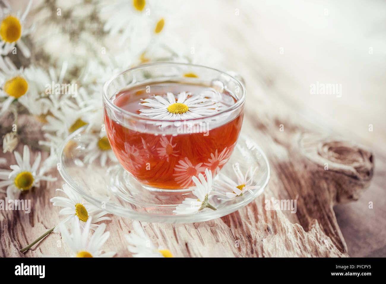 Borrar una taza de té de manzanilla medicinal sobre una mesa de madera antigua. Concepto de salud y estilo de vida saludable. Imagen De Stock