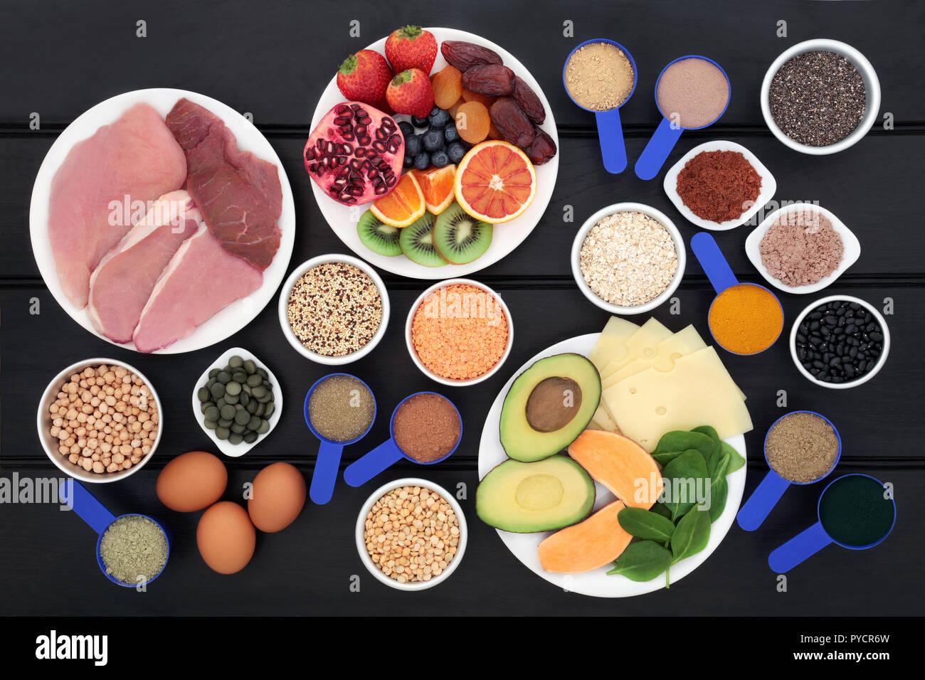 Alimentos saludables para los constructores del cuerpo con alto contenido  en proteínas como la carne, los productos lácteos, suplemento dietético en  polvo, tabletas de Chlorella, granos, cereales, fruta, verduras Fotografía  de stock -