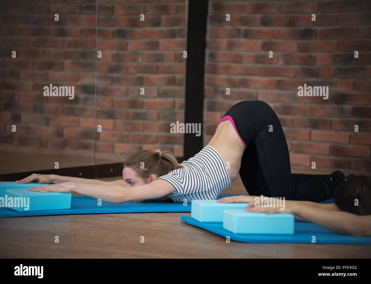 Young Pretty Woman con leggings realizando una baja backbend mostrando flexibilidad Imagen De Stock