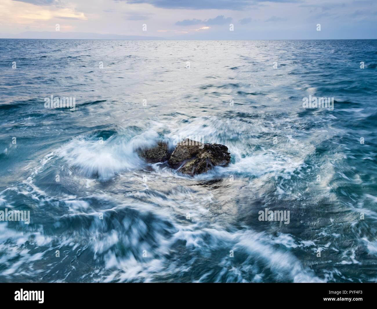 Las olas del mar golpeando dinámica rock mediados de larga exposición Foto de stock