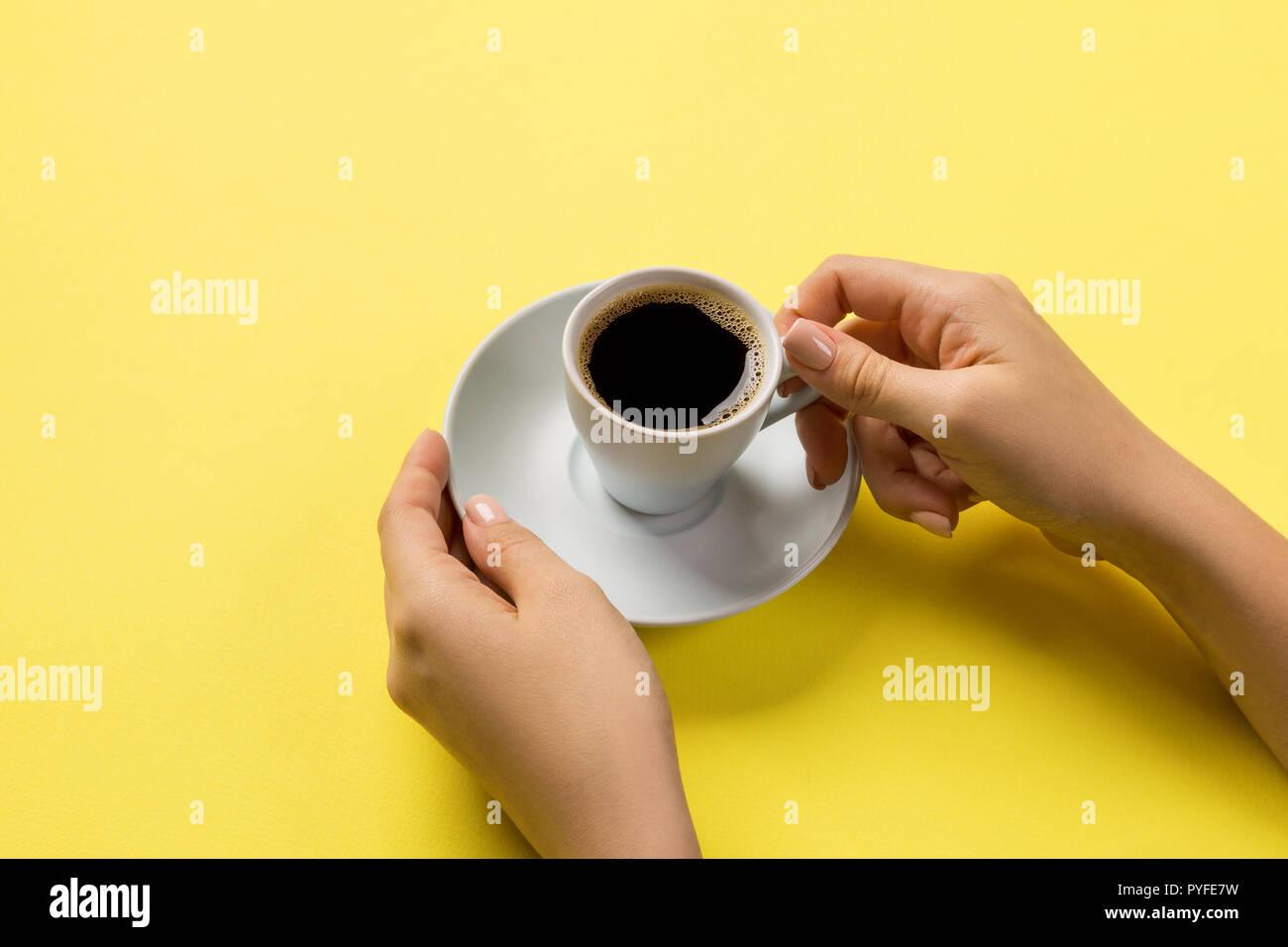 Estilo minimalista mujer mano sujetando una taza de café sobre fondo amarillo. Sentar planas, vista superior. Imagen De Stock