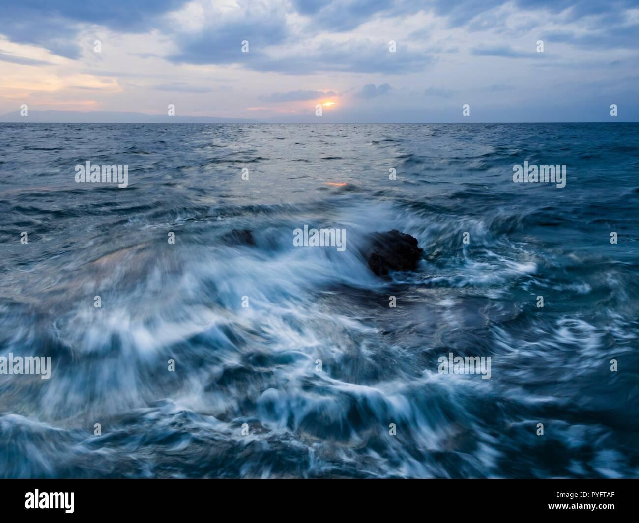 Las olas del mar golpeando dinámica rock casi-larga exposición Foto de stock