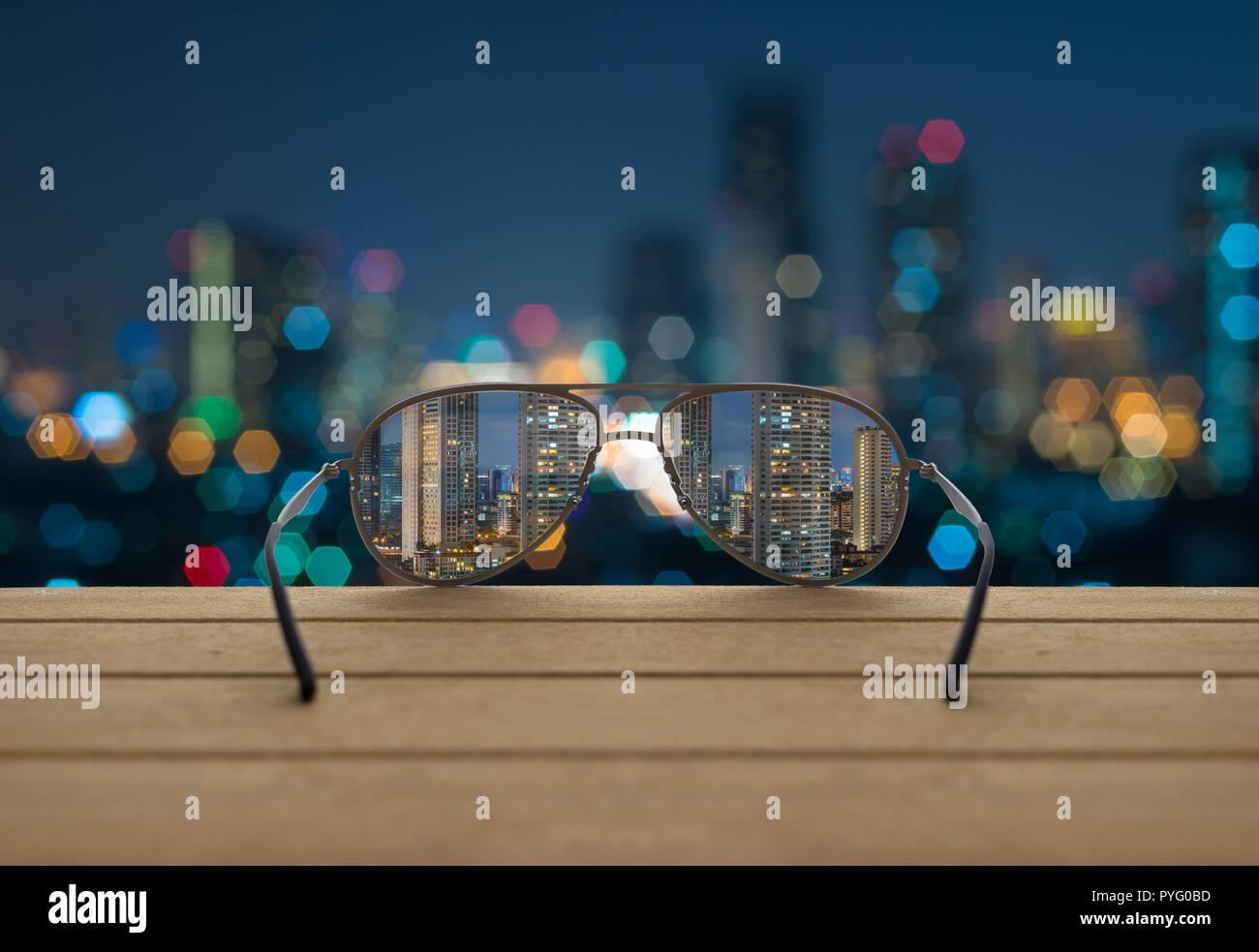 ef49f3c54a Paisaje urbano centrado en las lentes de las gafas en la madera a través de  la