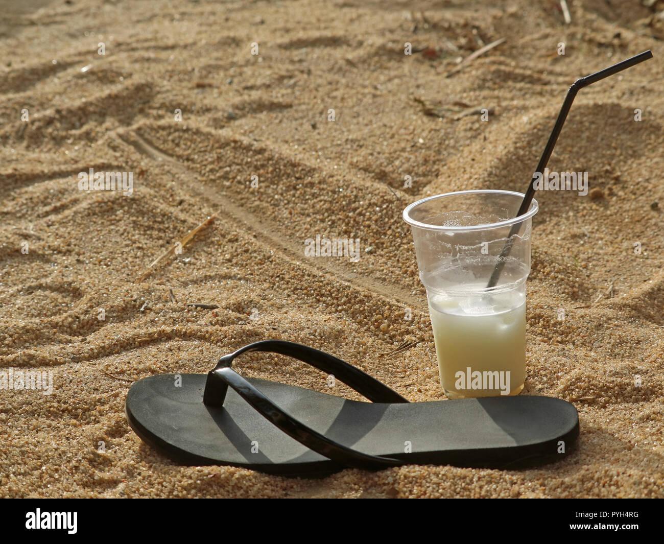 e1c8c0c480330 Playa negra única zapatilla y cóctel en un vaso de plástico con paja para  beber en