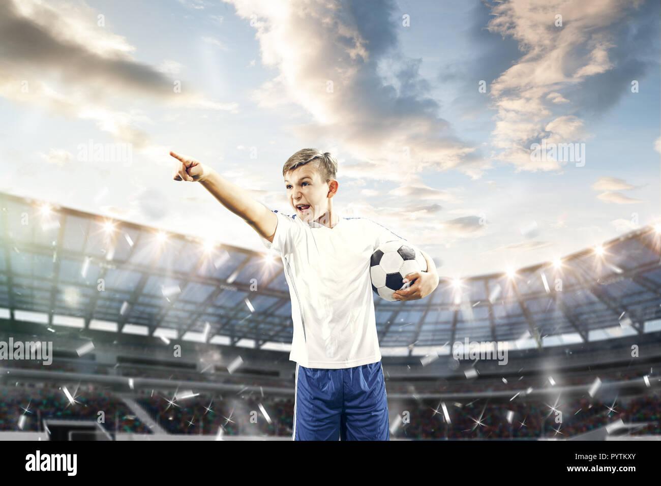Joven con una pelota de fútbol haciendo patada voladora al estadio. fútbol  los jugadores en 94177e9d206b3