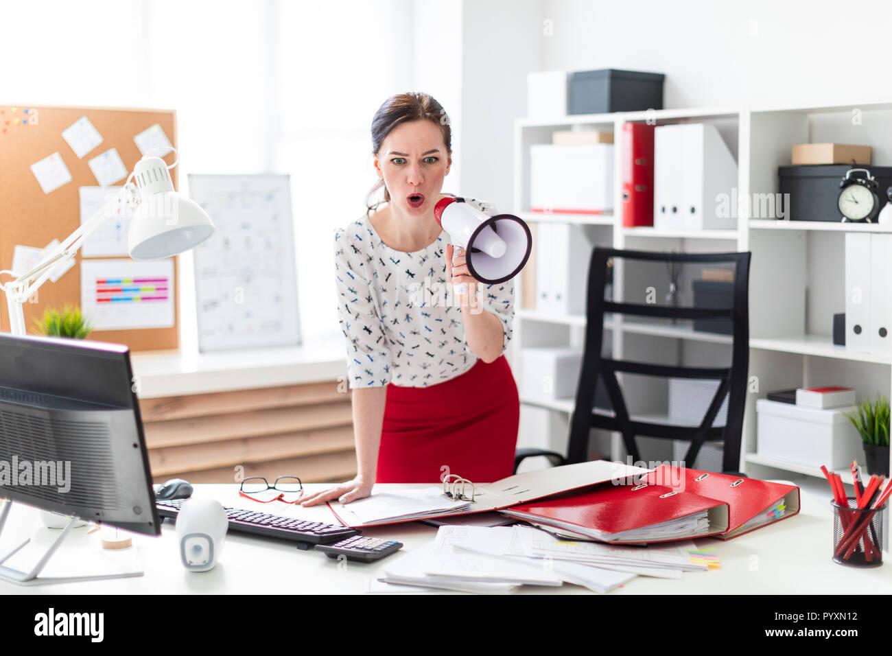 Una niña se encuentra en la oficina cerca de la mesa y dice en un grito. Imagen De Stock