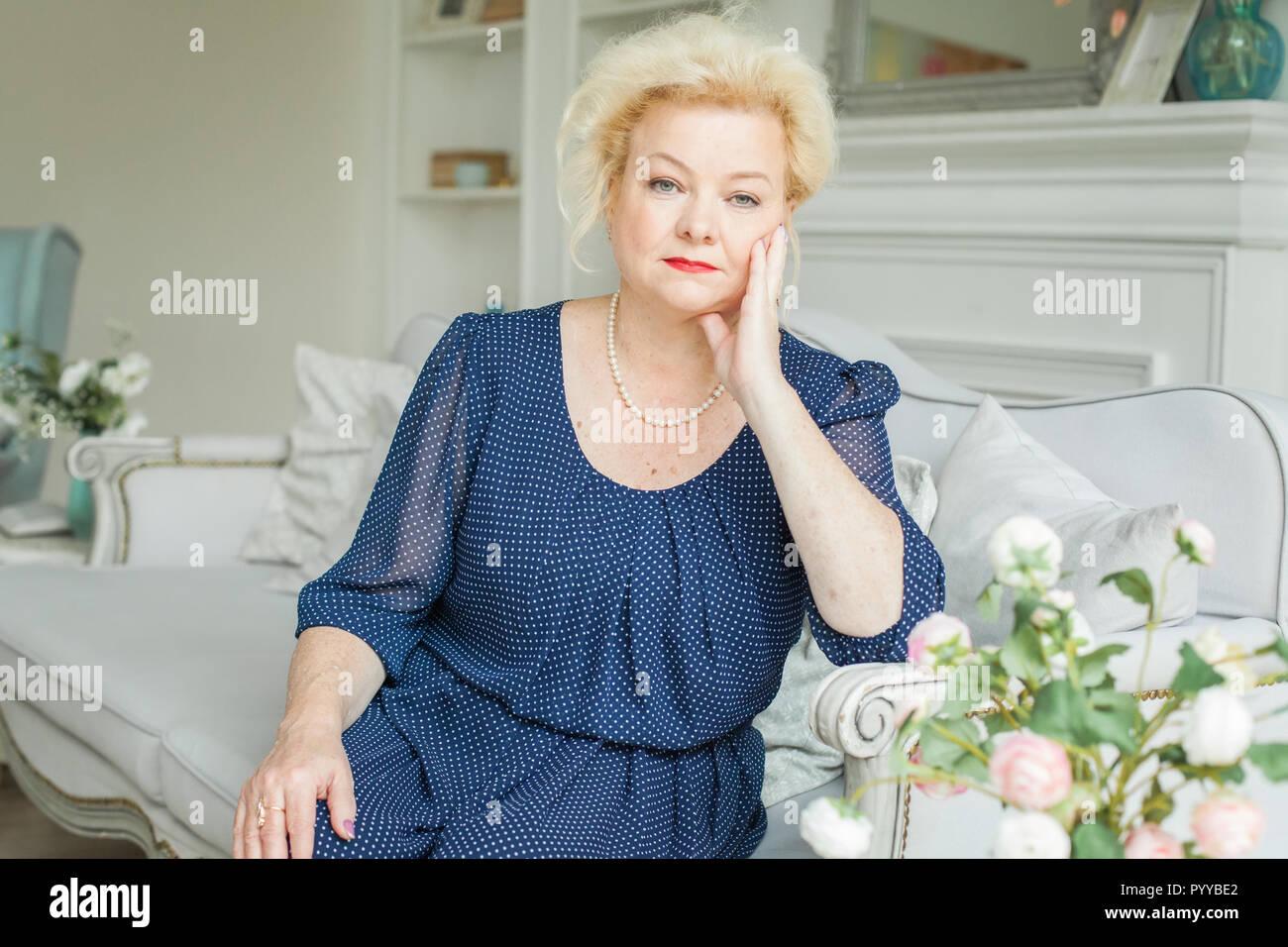 Retrato de mujer anciana rubia en casa, de 60 años de edad Imagen De Stock