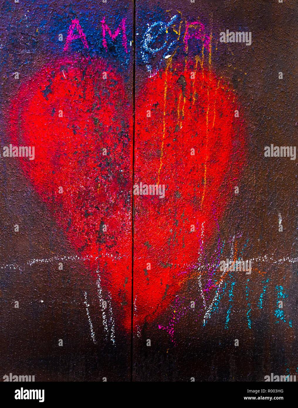 Corazón rojo sobre una puerta metálica oxidada y el wor: 'amor'. Imagen De Stock