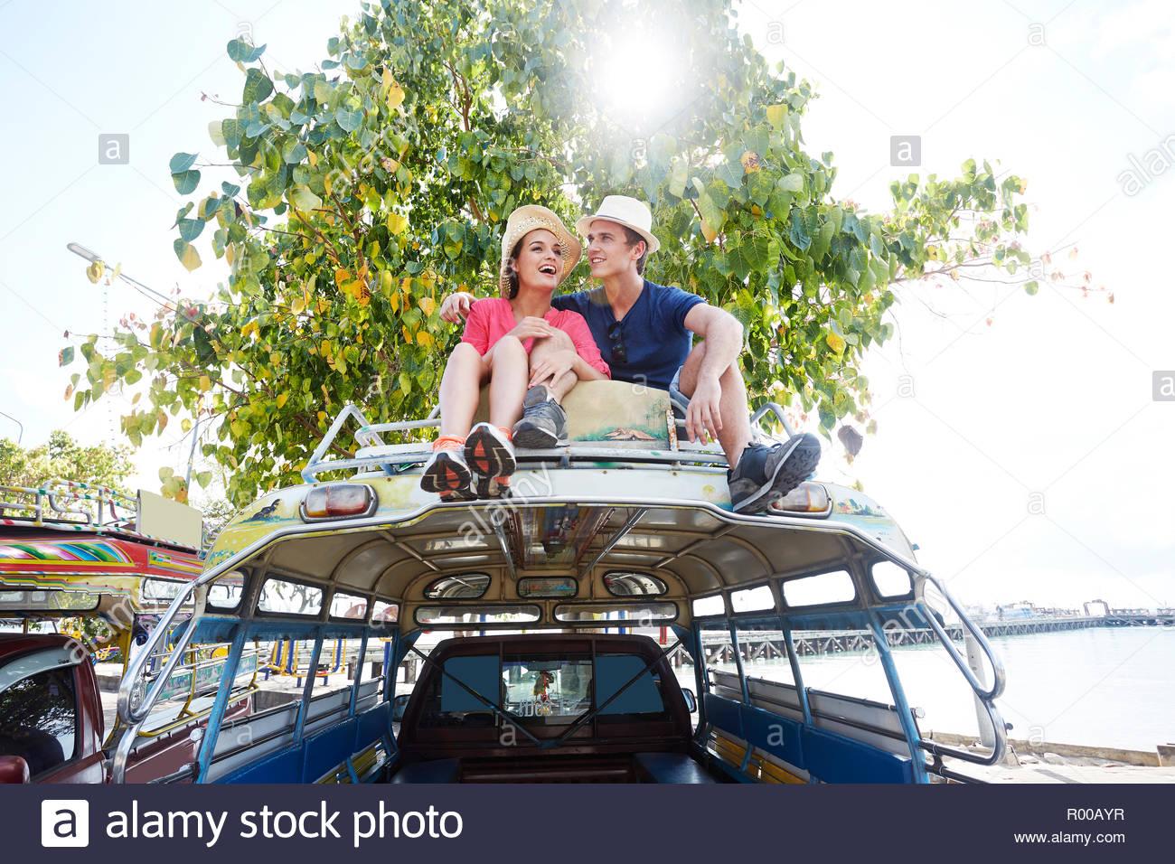 Pareja joven sentado en el techo del bus tour Imagen De Stock