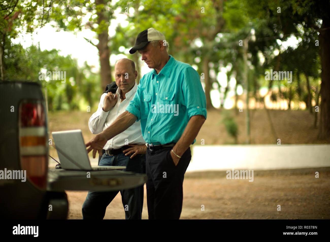 Agricultor muestra algo sobre un laptop a un empresario. Imagen De Stock