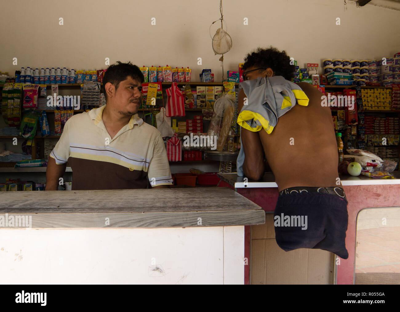 """Barranquilla, Colombia. 21 Oct, 2018. Alfonso Mendoza (r) de Venezuela, habla con el dueño de una pequeña tienda en la ciudad colombiana de Barranquilla. Mendoza nació sin piernas, pero él nunca dejaba de estar parado. A los 25 años es un skater, surfer y rapero y recientemente se ha convertido en un padre. Al igual que cientos de miles de sus compatriotas, el venezolano huían del hambre, la miseria y la opresión en su natal Venezuela. (Dpa """"contra todas las fronteras: los venezolanos sin piernas lucha por la normalidad"""" de 02.11.2018) Credit: Natalia Ortiz Mantilla/dpa/Alamy Live News Foto de stock"""