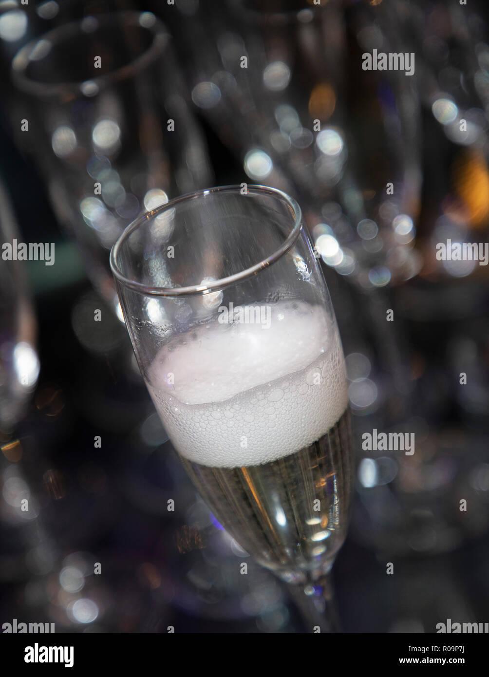Copa de vino espumoso sólo derramado con un burbujeante cabeza. Bokeh de fondo borroso, Imagen De Stock