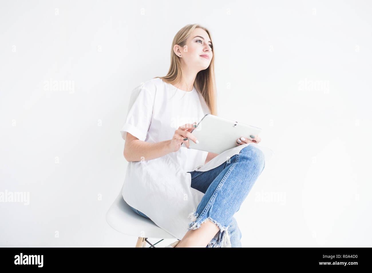 87290640f1 Retrato de una joven chica rubia elegante en una camiseta blanca y  pantalones de mezclilla con una tableta sobre un fondo blanco.
