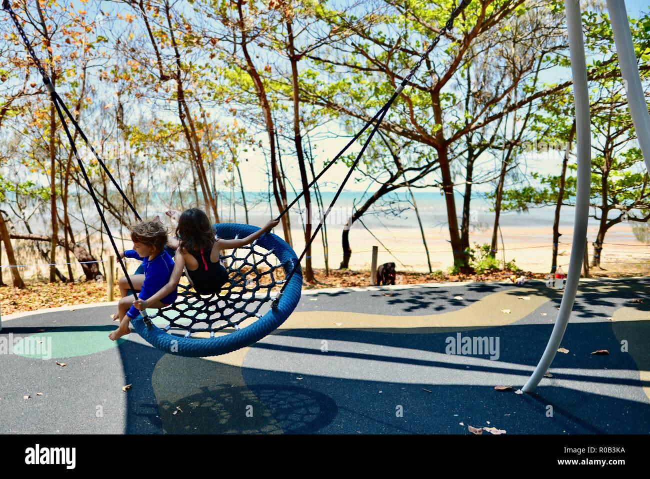 Dos niños jugando en un columpio, nido Balgal beach, Queensland, Australia Foto de stock