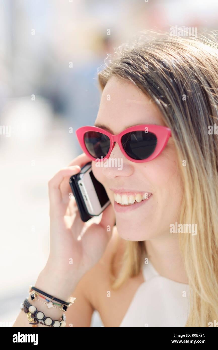 Un joven holandés (Caucásicos) mujer que utiliza su teléfono móvil en la calle en un día soleado Imagen De Stock