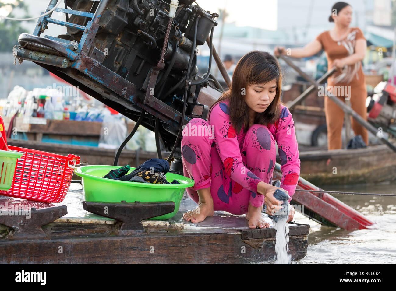 CAN THO, Vietnam, 12 de diciembre de 2014:Una mujer está lavando la ropa a bordo de un barco comercial en El Cai Rang mercado flotante sobre el río Mekong i Foto de stock