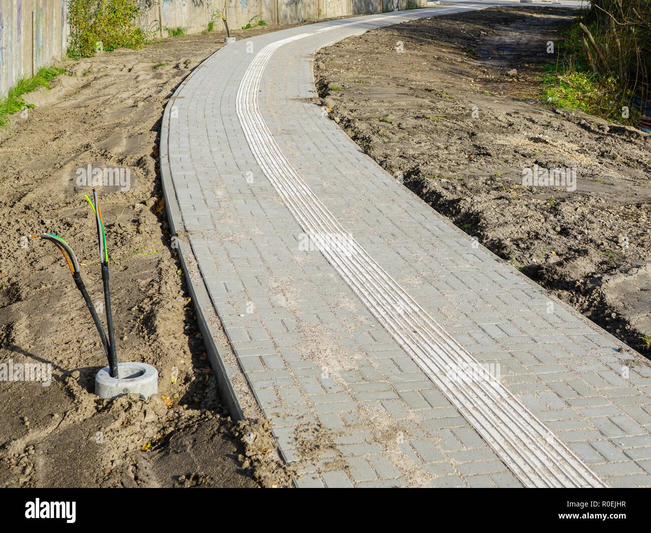 Pavimento pavimento nuevo con directrices integradas para las personas con discapacidad visual Imagen De Stock