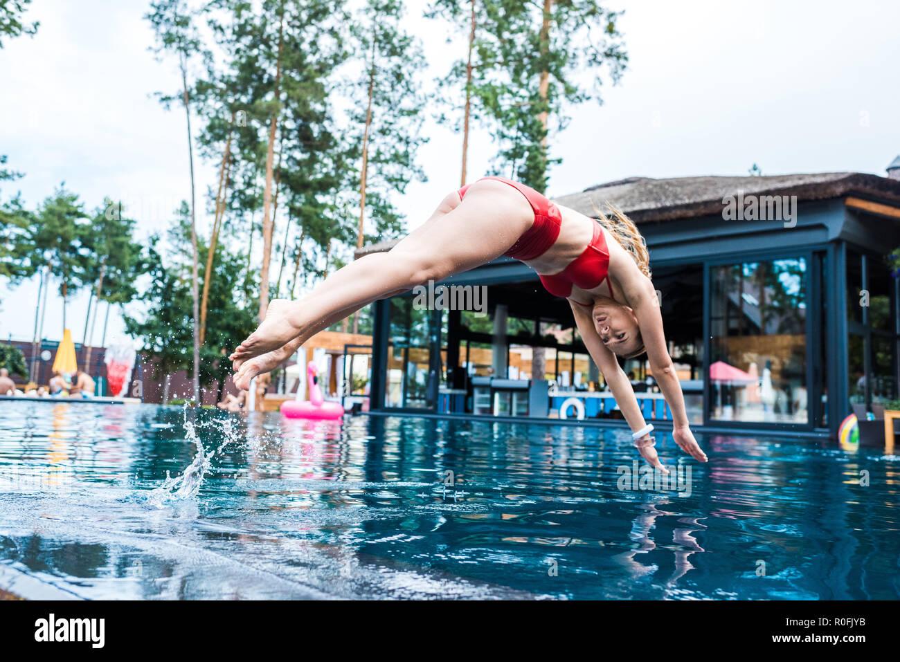 Mujer joven en bañador rojo saltando a la piscina Imagen De Stock