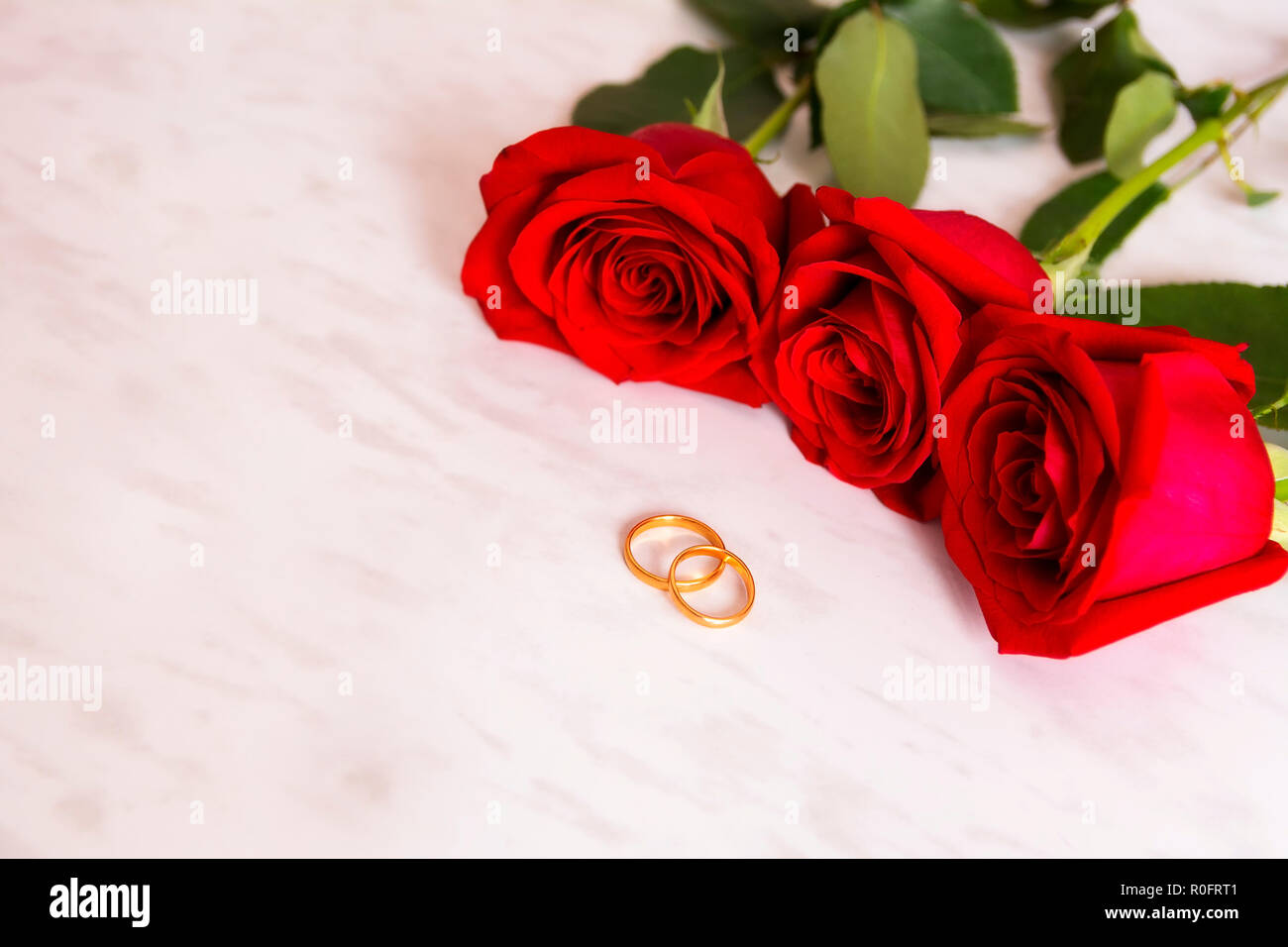 7bcc9f054ad9 Dos anillos de boda de oro y tres rosas rojas. Invitación de boda ...