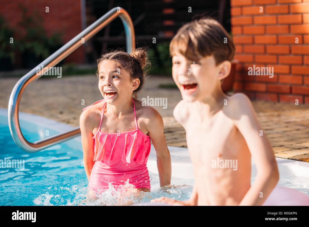 Poco emocional hermanos nadando en la piscina junto a día de verano Imagen De Stock