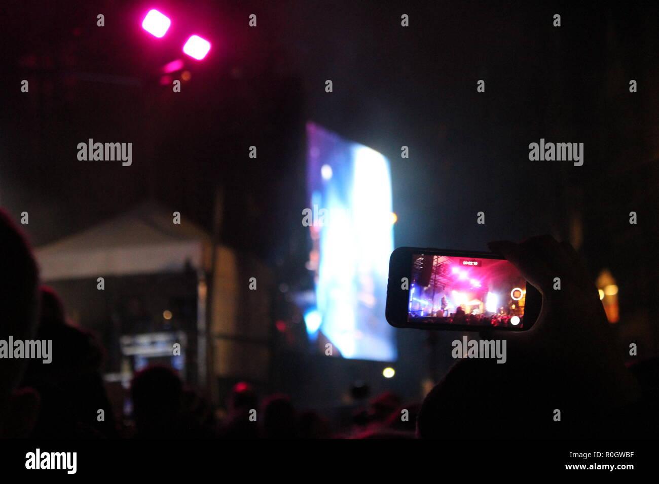 Teléfono inteligente en un concierto de música - observando un rendimiento a través de un teléfono celular Foto de stock