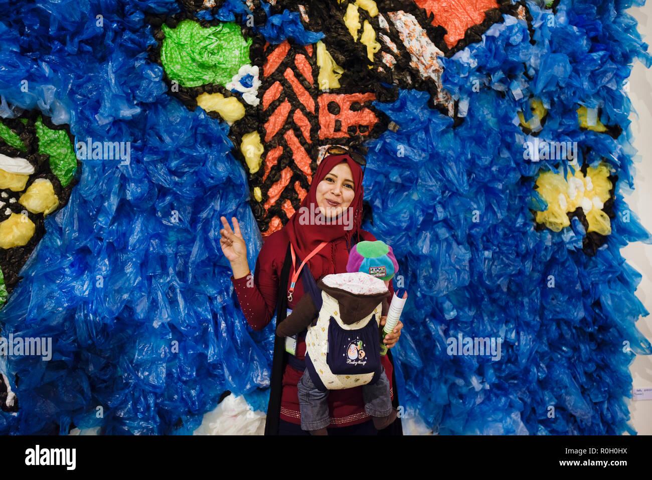 Mujer magrebí y su bebé posando delante de un mapa del mundo hecho de bolsas de plástico reciclado a la Conferencia de las Naciones Unidas sobre el Cambio Climático Imagen De Stock