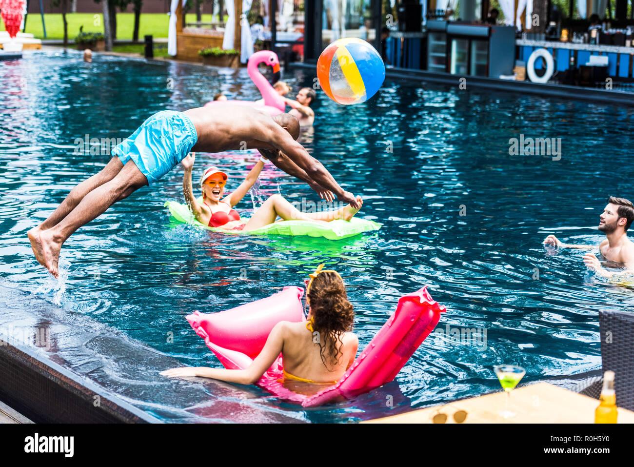 Joven saltando en la piscina mientras sus amigas descansando en colchones inflables Imagen De Stock