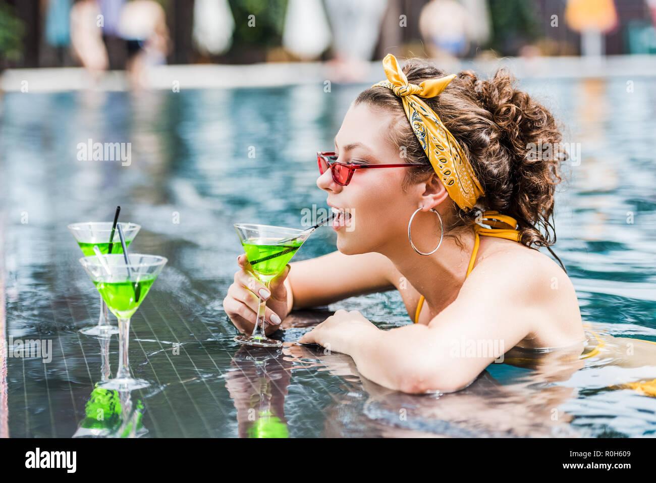 Atractiva mujer joven beber cócteles en la piscina Imagen De Stock