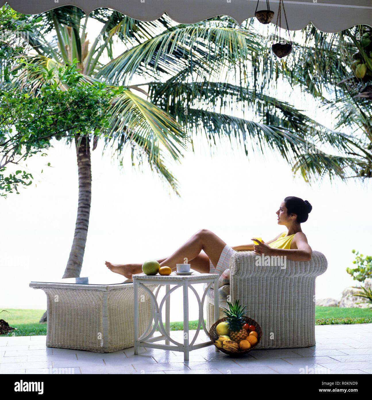 Mujer joven relajándose en el sillón de mimbre blanco, terraza, jardín tropical, palmeras, Guadalupe, Antillas Francesas, Foto de stock