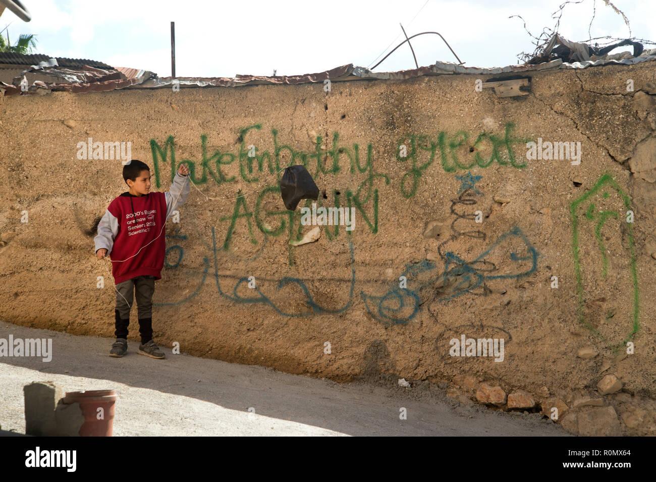 """Belén. Palestina. Un chico juega con una cometa hecha de una bolsa de plástico negra, en la parte delantera de la Escritura diciendo 'make empatía gran nuevamente"""". Imagen De Stock"""