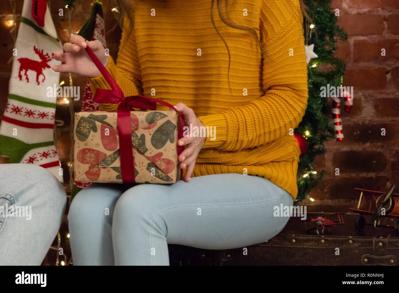 La chica en un suéter amarillo se desajusta un regalo de Navidad Imagen De Stock