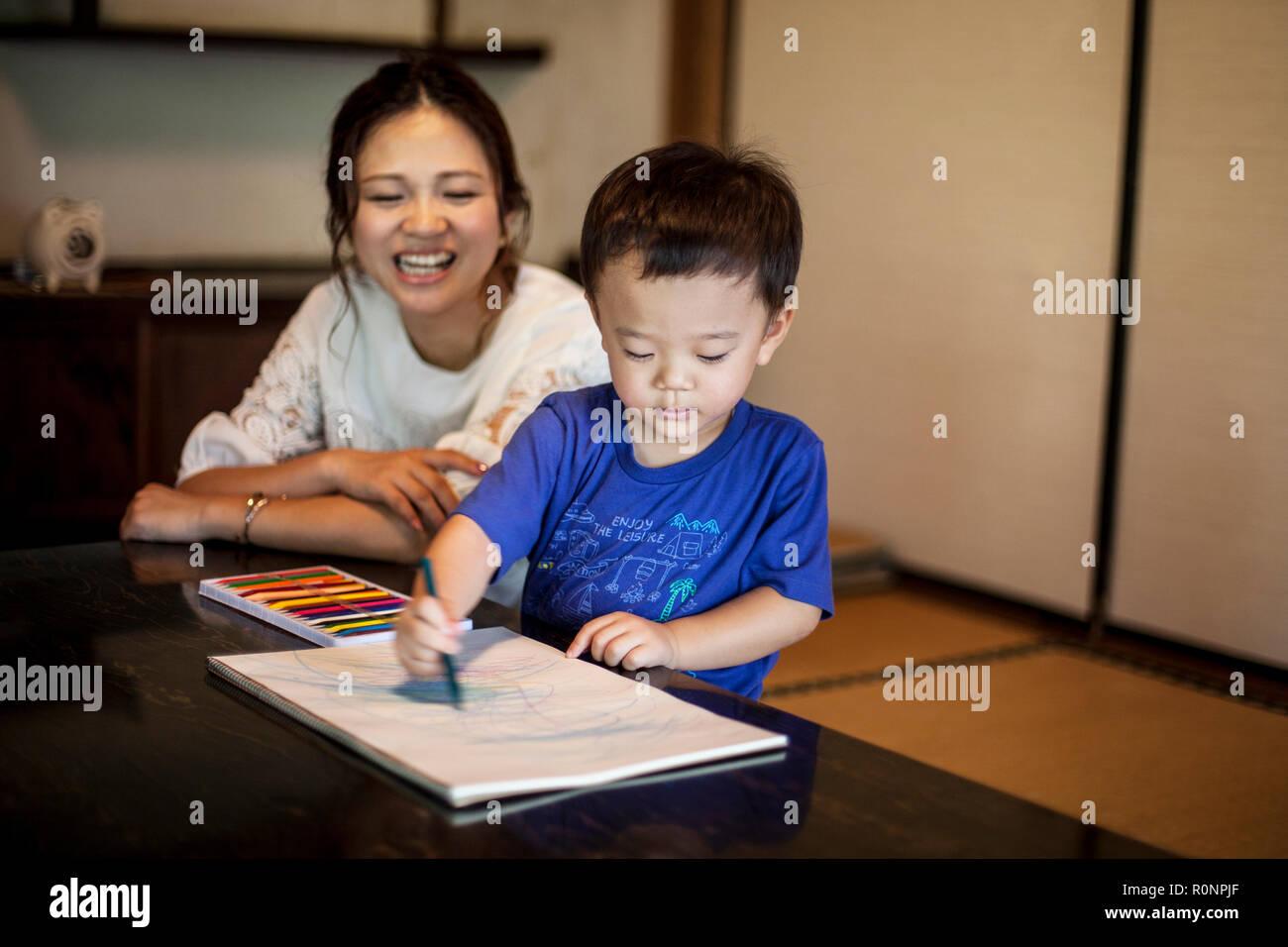 Sonriente Mujer Japonesa Y El Niño Sentado En Una Mesa Dibujo Sobre