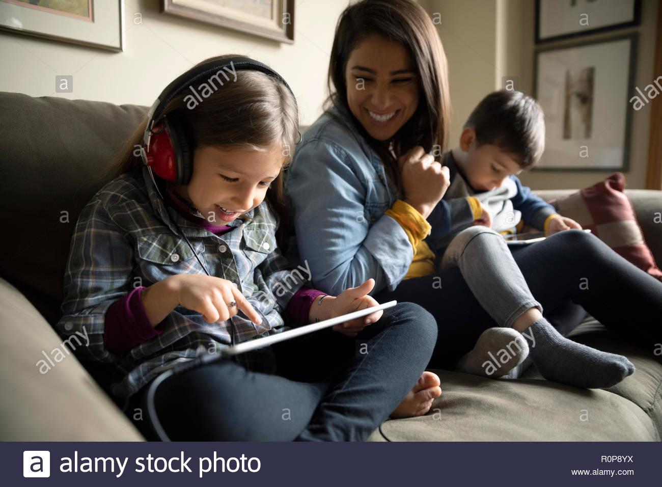 Madre Latinx viendo niños usando tabletas digitales en el sofá Imagen De Stock