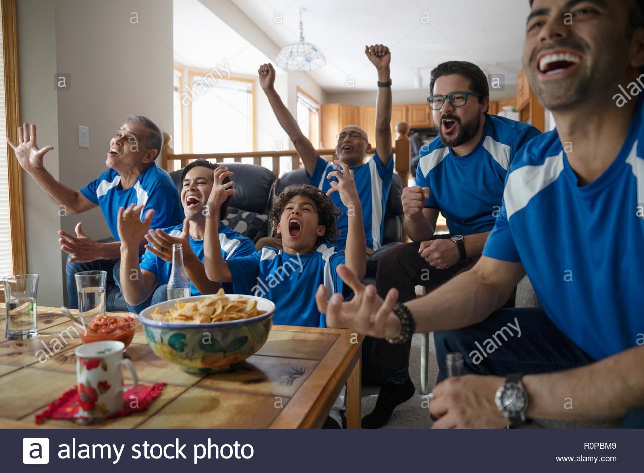 Multi-familia Latinx generación viendo deportes y vítores Foto de stock