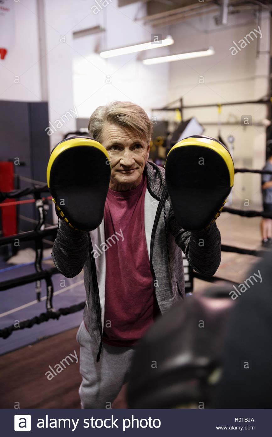 Entrenador masculino con almohadillas de boxeo en el gimnasio Imagen De Stock