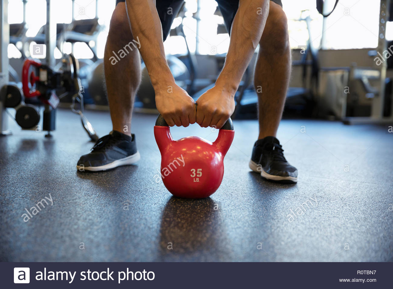 El hombre ejerciendo con kettlebell en gimnasio Imagen De Stock