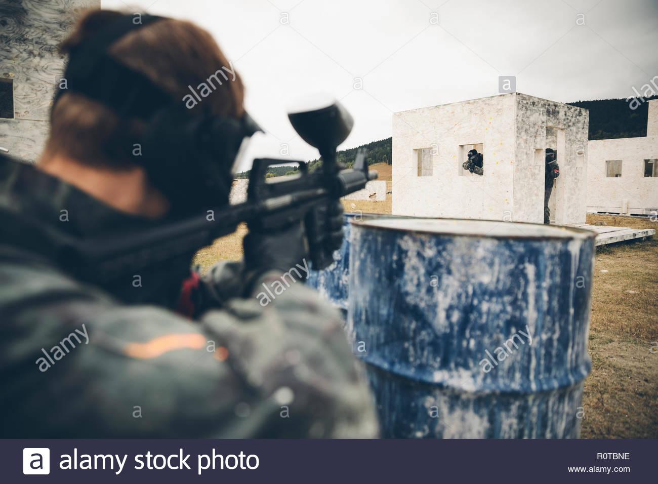 El hombre detrás de paintball barril Imagen De Stock