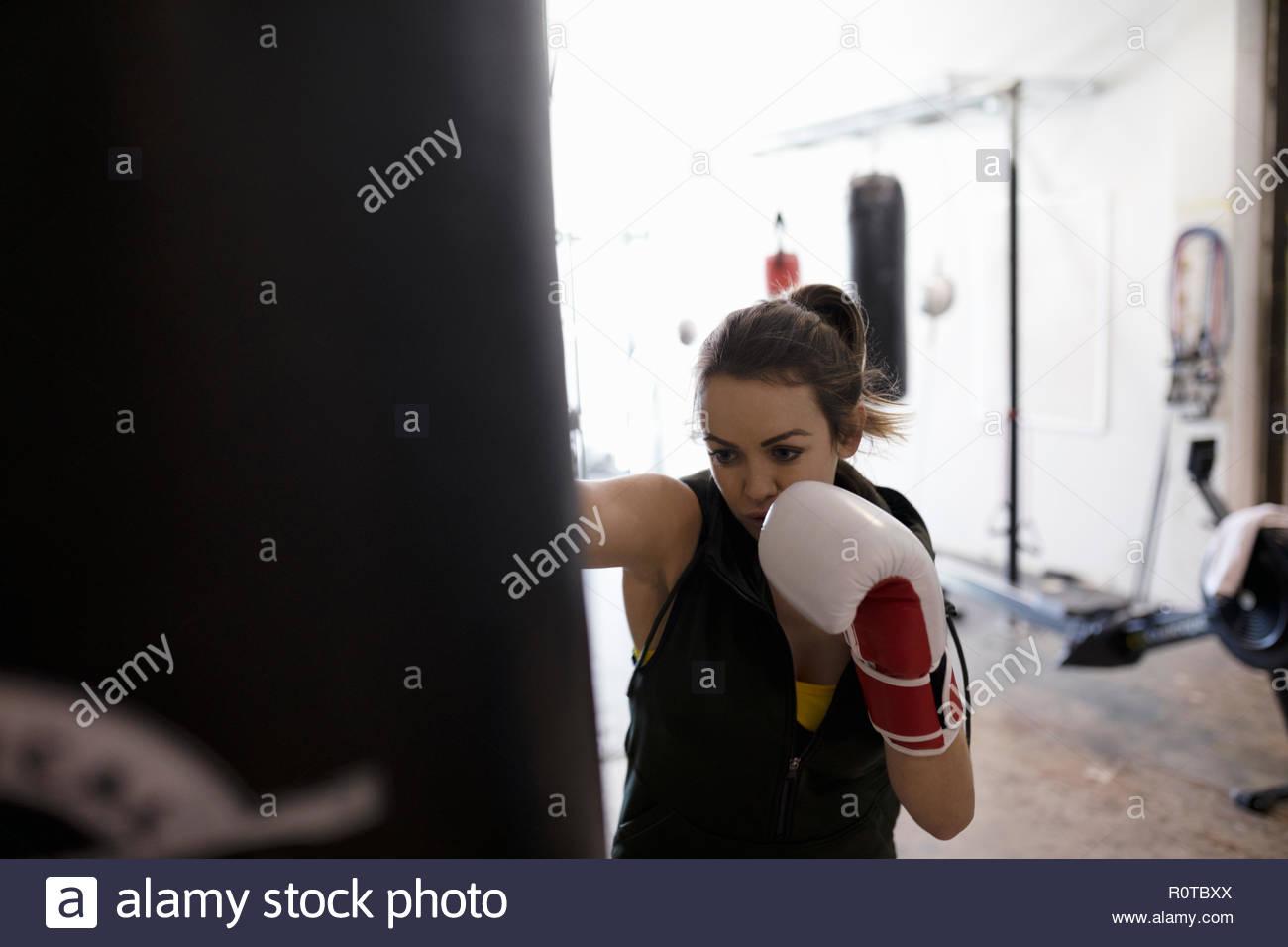 Boxer hembra dura formación en saco de boxeo en el gimnasio Imagen De Stock