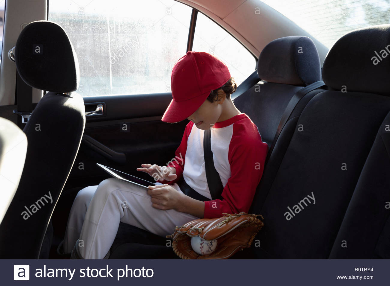 Boy en el béisbol uniforme utilizando digital comprimido en el asiento de atrás del coche Imagen De Stock