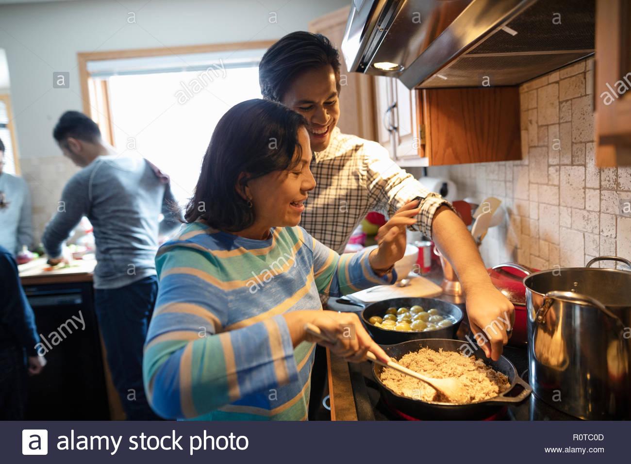 Latinx madre e hijo adulto cocinar en estufa en la cocina Imagen De Stock