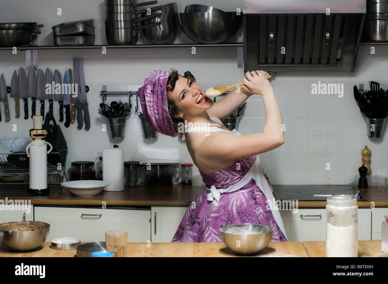 Hermosa niña cocineros en la cocina, crema en una cuchara de madera, cerca de la boca, mira a la cámara Imagen De Stock