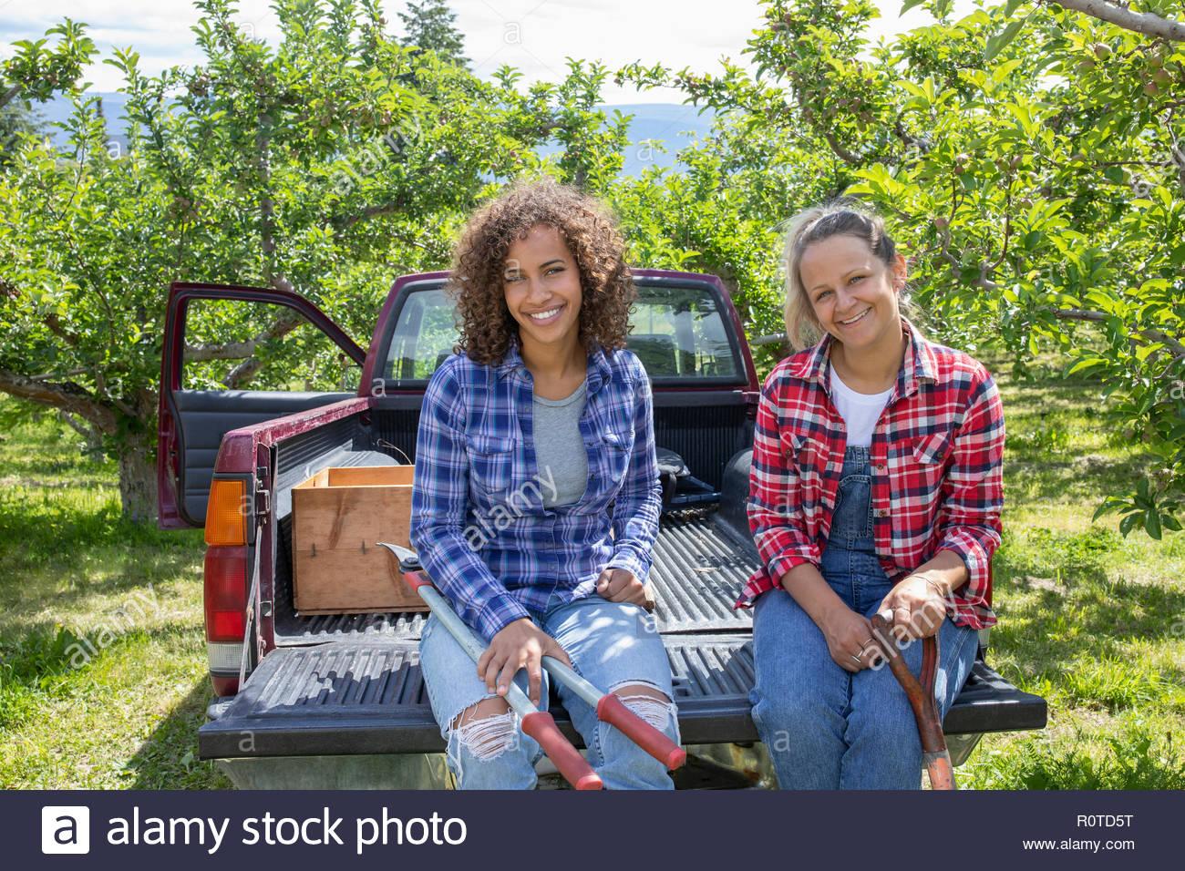 Retrato sonriente, confiados a las agricultoras sentado en la parte trasera de la carretilla en huerto Imagen De Stock
